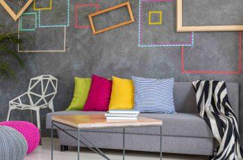 sala no estilo color blocking, com sofá e parede cinza, almofadas coloridas - cores inverno 2018 para decoração de interiores